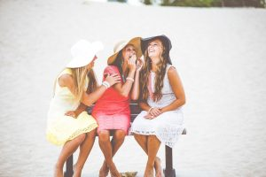 Three Female Friends Laughing and Telling Secrets