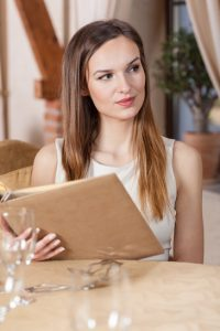 Woman sitting in a restaurant alone holding menu