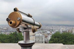 A telescope viewer overlooks view Paris skyline.