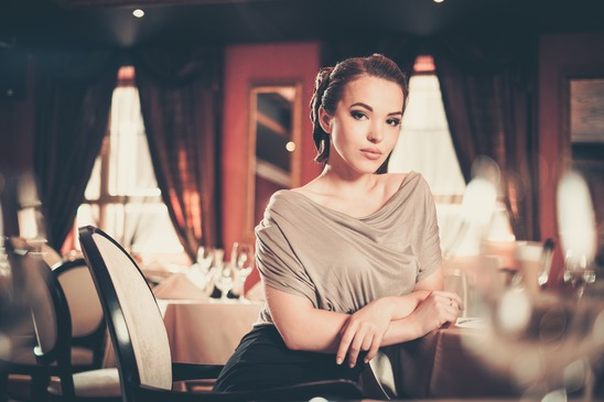 Beautiful young woman alone in a restaurant.