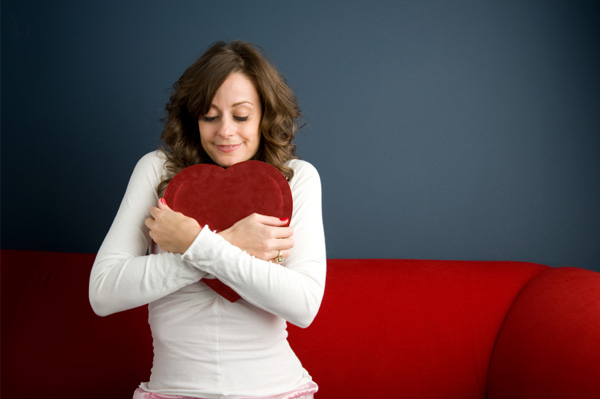 woman hugging her pillow, woman expressing self love, woman who is happy and approves of self.