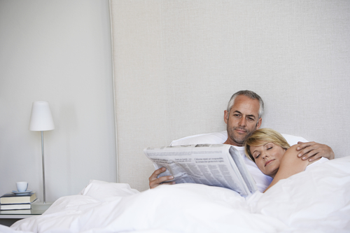 dating in your 40s couple in bed with newspaper