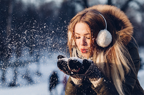 woman blowing single problems away in snow