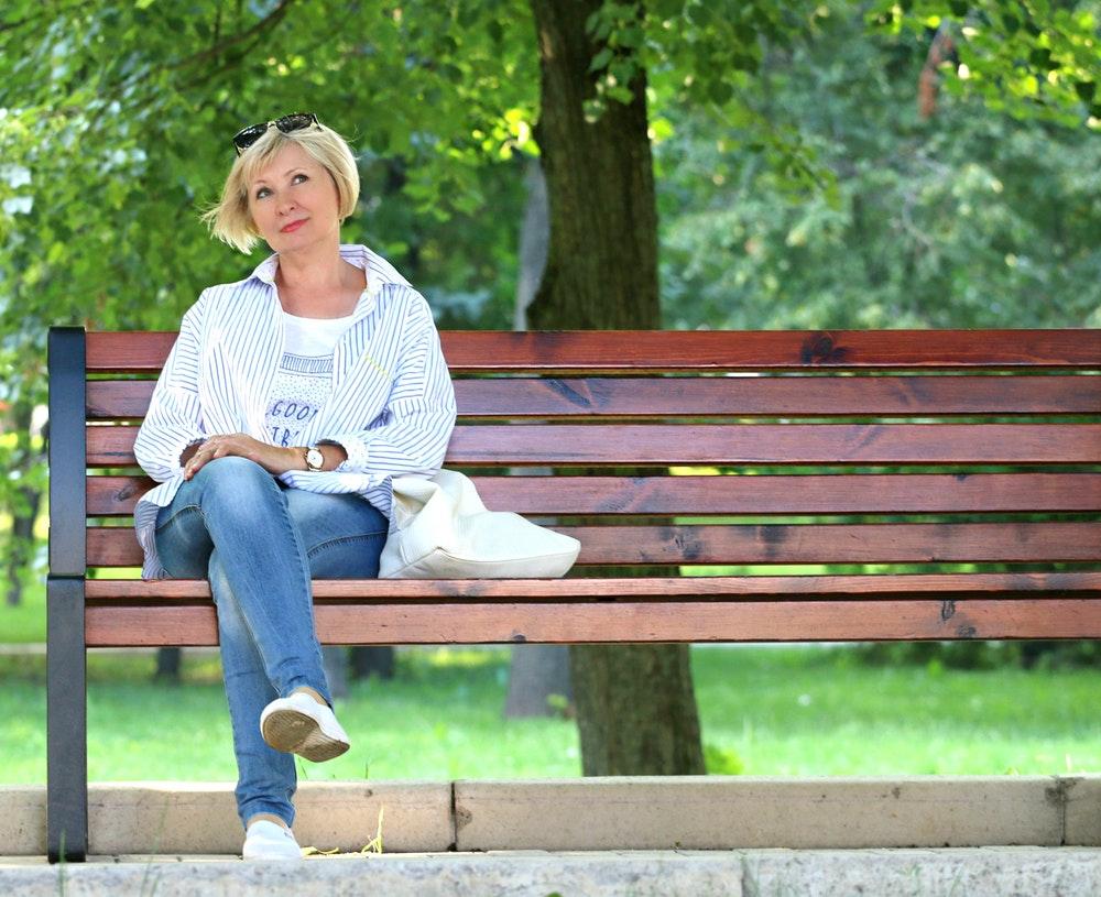 pretty woman feeling old on parkbench