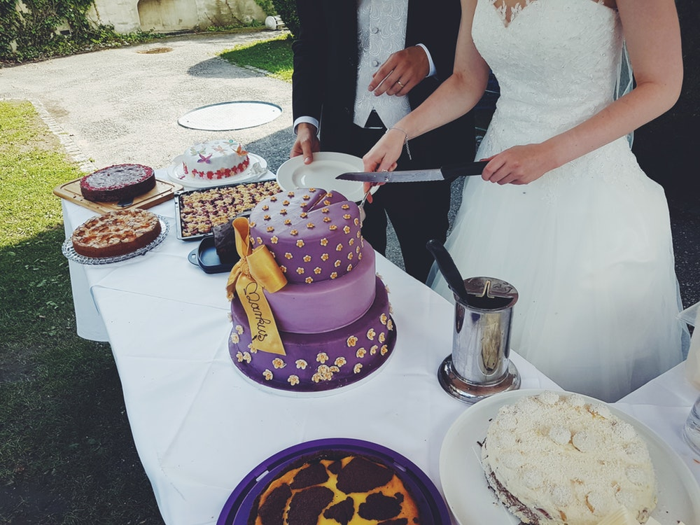 bride and groom cutting purple cake